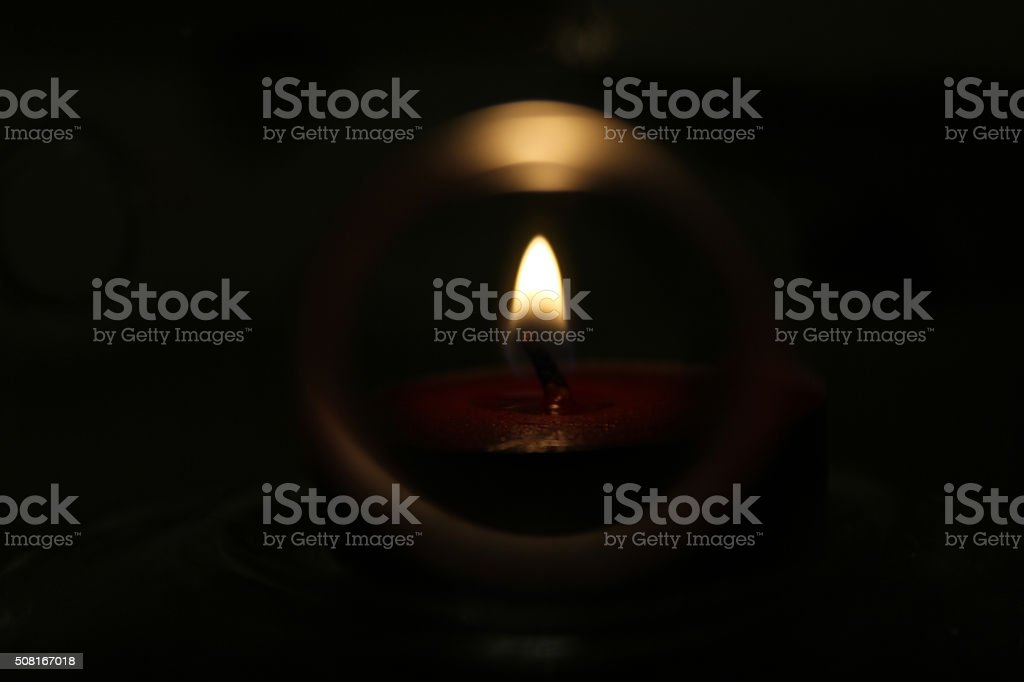 Candlelight Casting Its Glow in a Dark Space stock photo