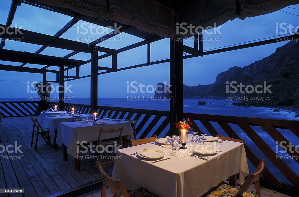 candlelight table in a restaurant on the sea at dusk royalty-free stock photo
