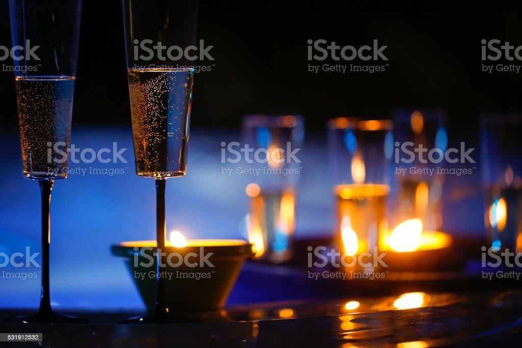 Candlelit champagne glasses beside a jacuzzi stock photo