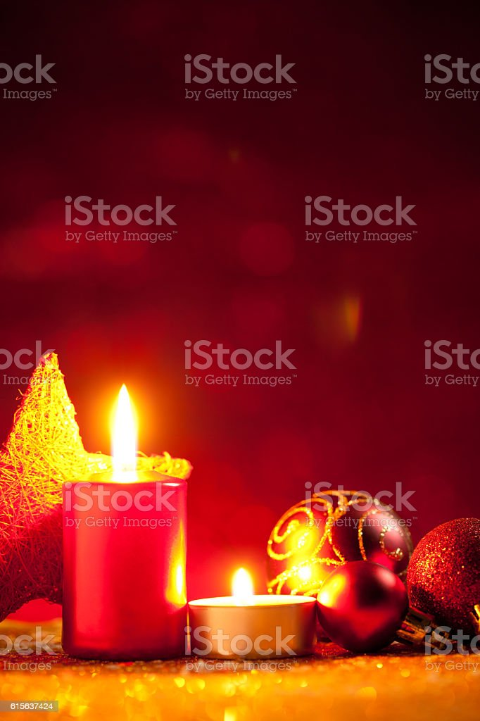 Candles and baubles on glitter with red background stock photo