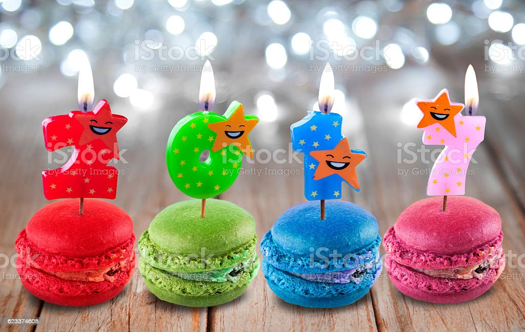 Candles and Macaroons 2017 in front Christmas lights. stock photo