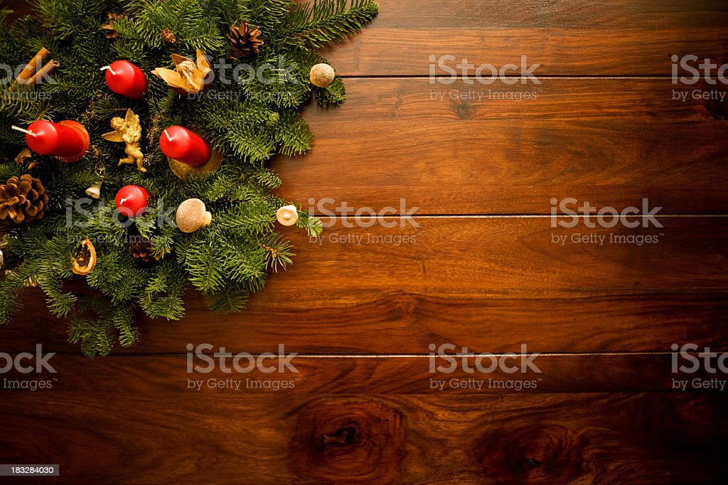 Candles and ornaments on Christmas leaves on wooden floors stock photo