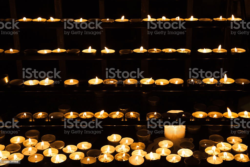 Candles burning on shelves in dark church stock photo