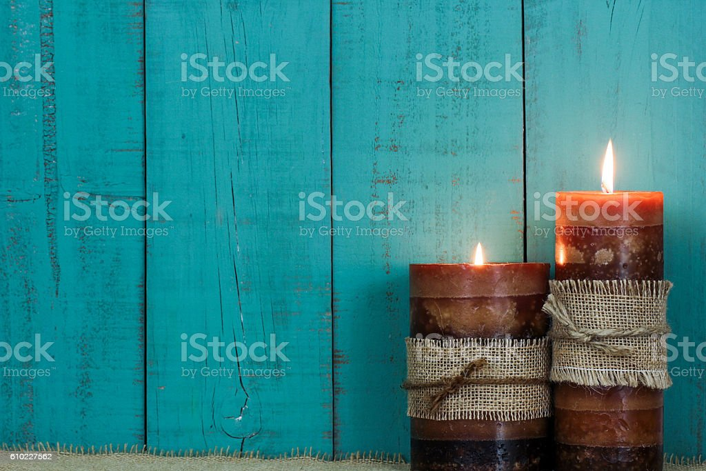 Candles by teal blue background stock photo