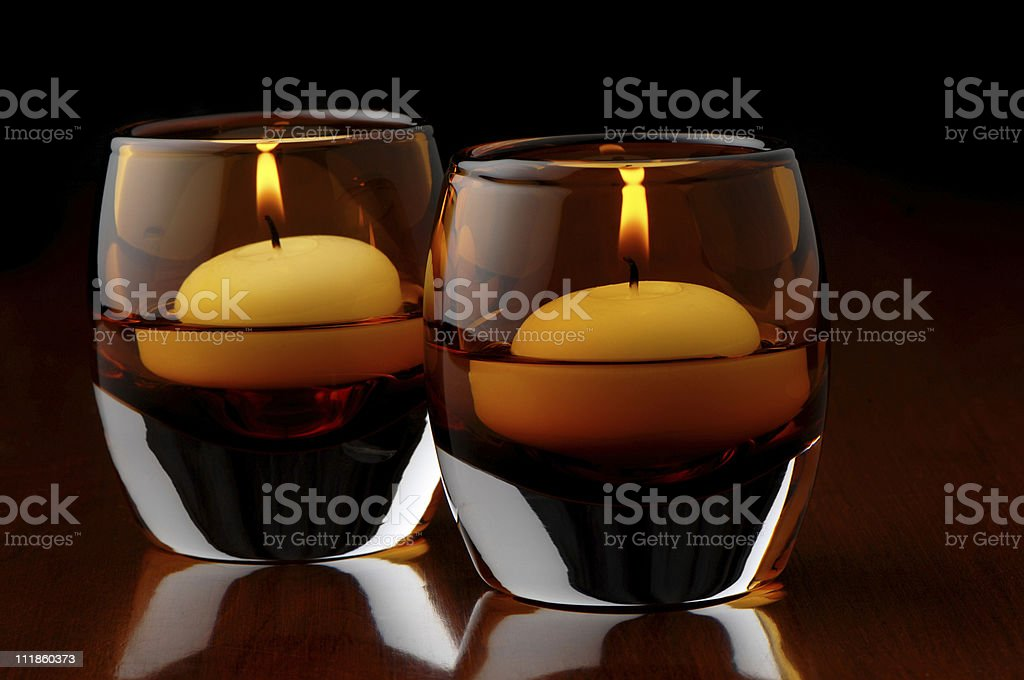 Candles Floating in Amber Glasses on Cherry Wood Table royalty-free stock photo