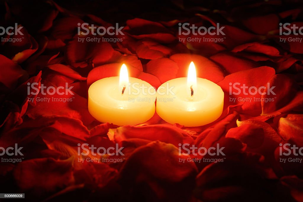 candles on rose petals stock photo