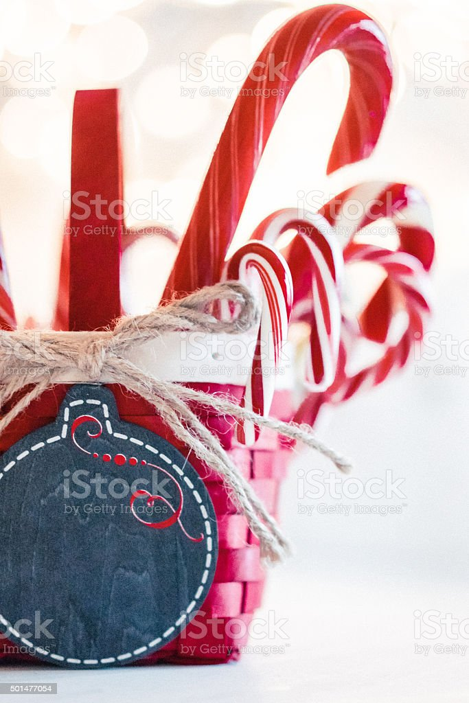 Candy canes in a basket on christmas background stock photo