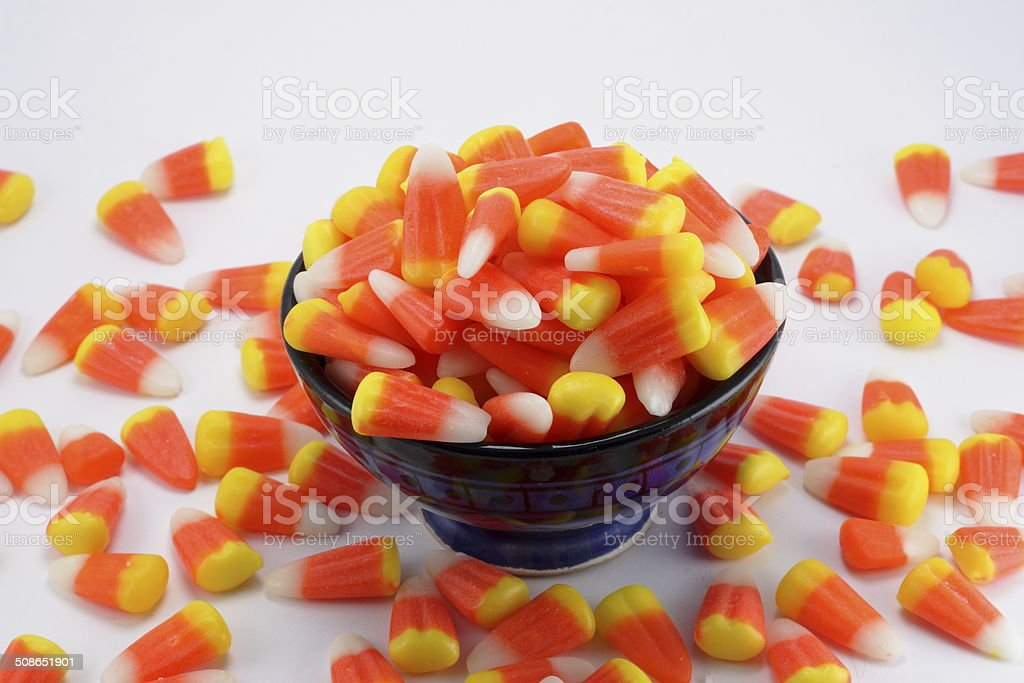 Candy Corn in a Blue Bowl With A White Background stock photo