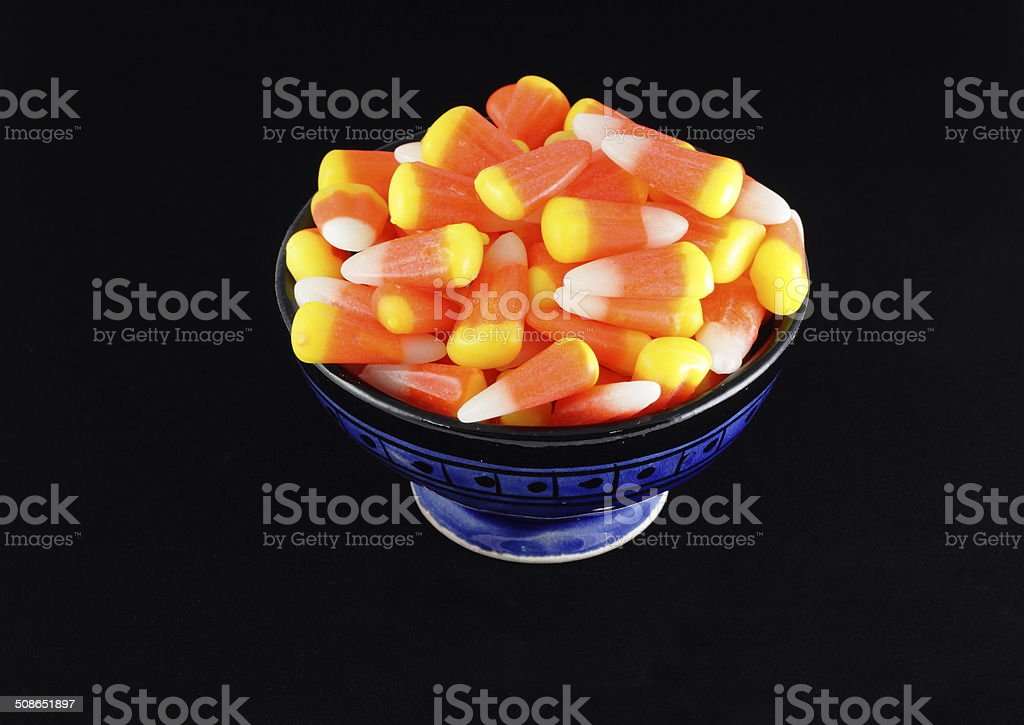 Candy Corn in a Blue Bowl With Black Background stock photo