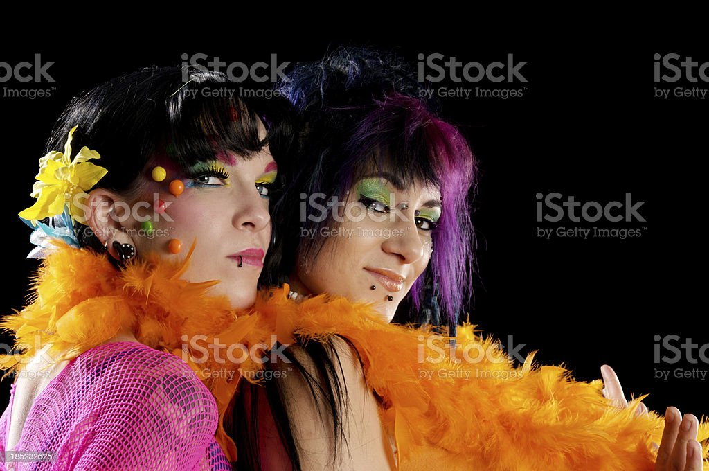 Candy girls spooning with orange feather boa. royalty-free stock photo