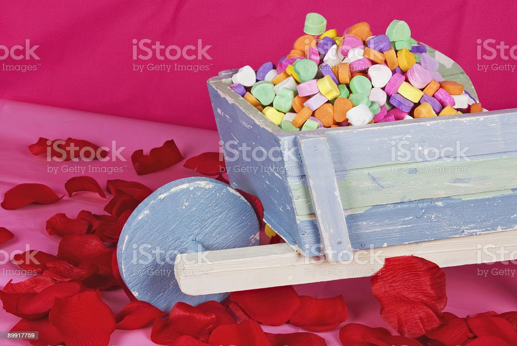 candy hearts in a wheelbarrow surrounded by rose petals royalty-free stock photo