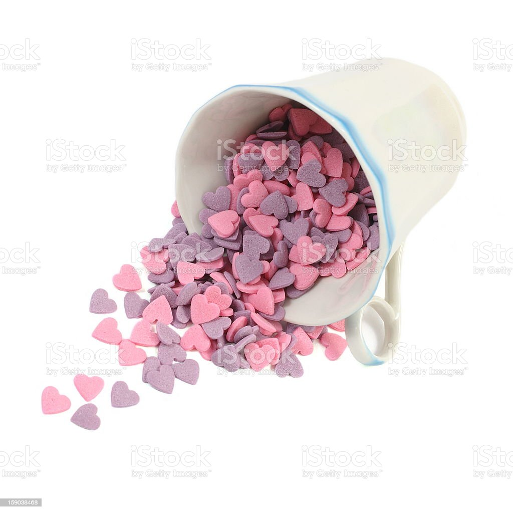 Candy hearts spill out of a coffee cup over white royalty-free stock photo