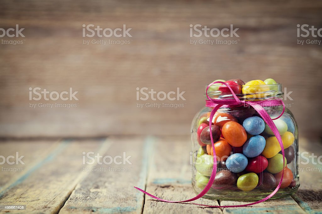 Candy jar decorated with a bow against rustic wooden background stock photo