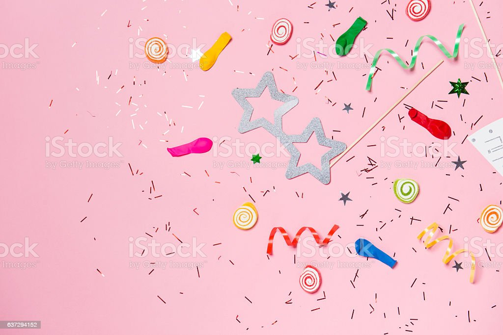 Candy with colorful party items on pink background. stock photo