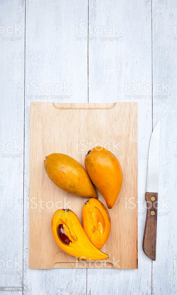 Canistel fruit on cutting board stock photo
