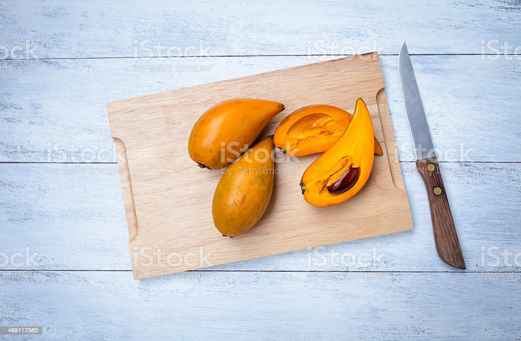 Canistel fruit on wooden cutting board stock photo