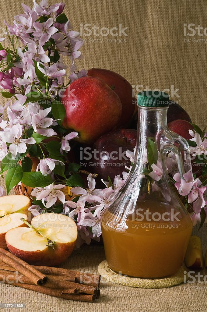 Canister of apple cider vinegar, cinnamon & flowers on table royalty-free stock photo