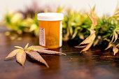 Cannabis leaf sitting next to prescription bottle of marijuana