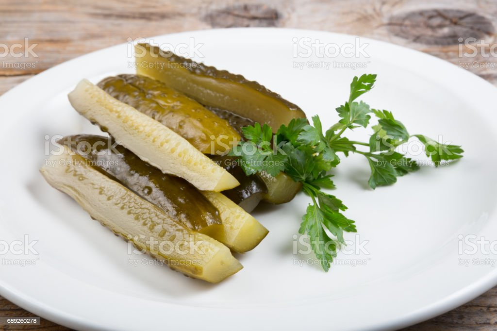 Canned cucumbers on a white plate stock photo