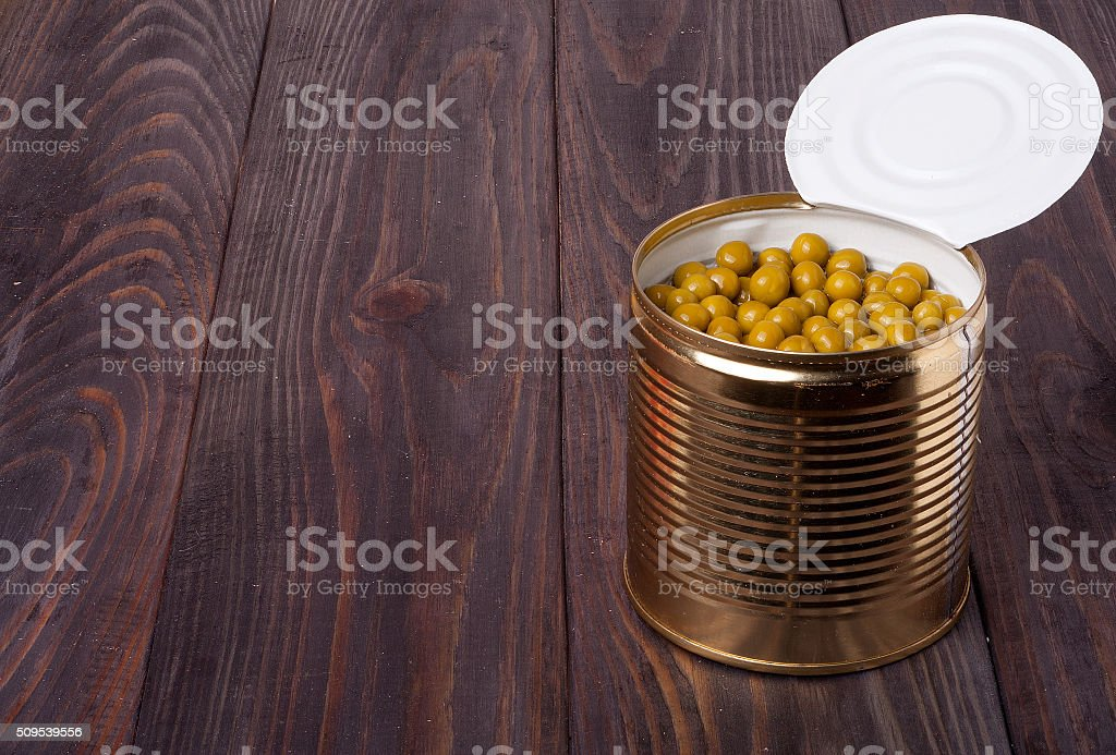 canned green peas in a bank on wooden table stock photo