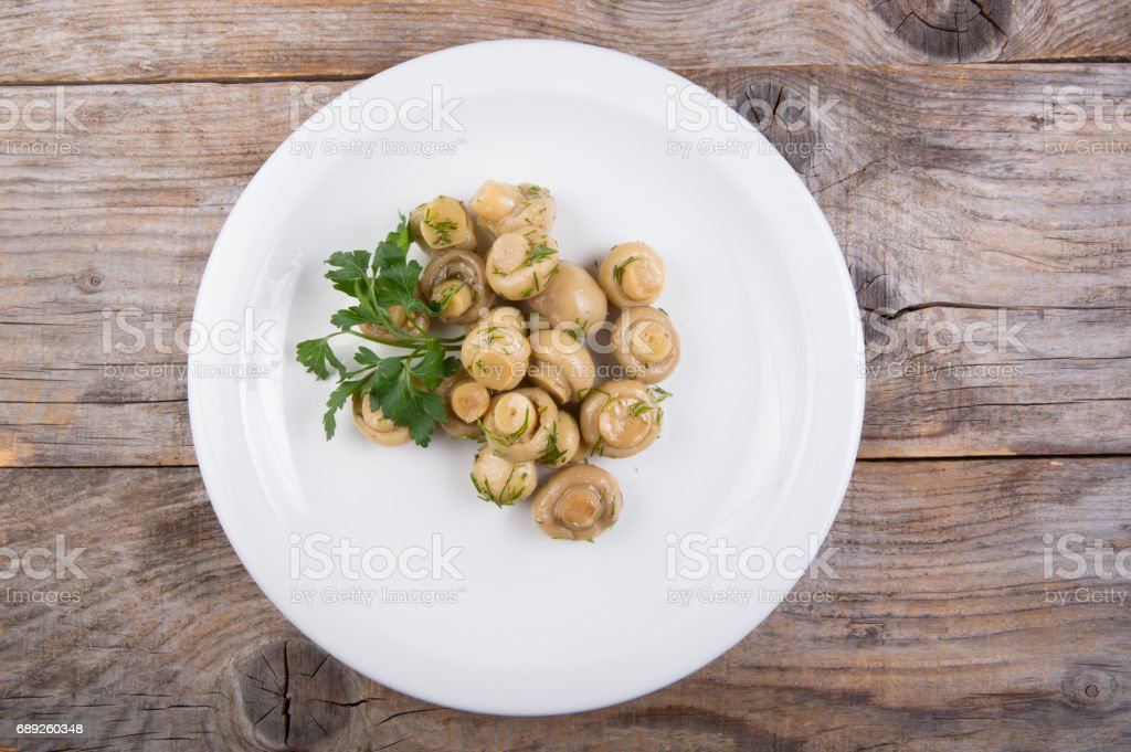 Canned mushrooms on a white plate stock photo