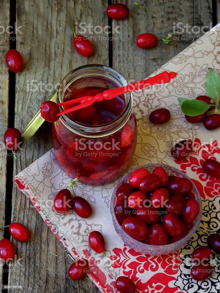 canned of dogwood (cornelian cherry berry) on wooden background. stock photo