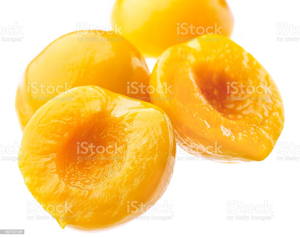 Canned peach on syrup over white background royalty-free stock photo