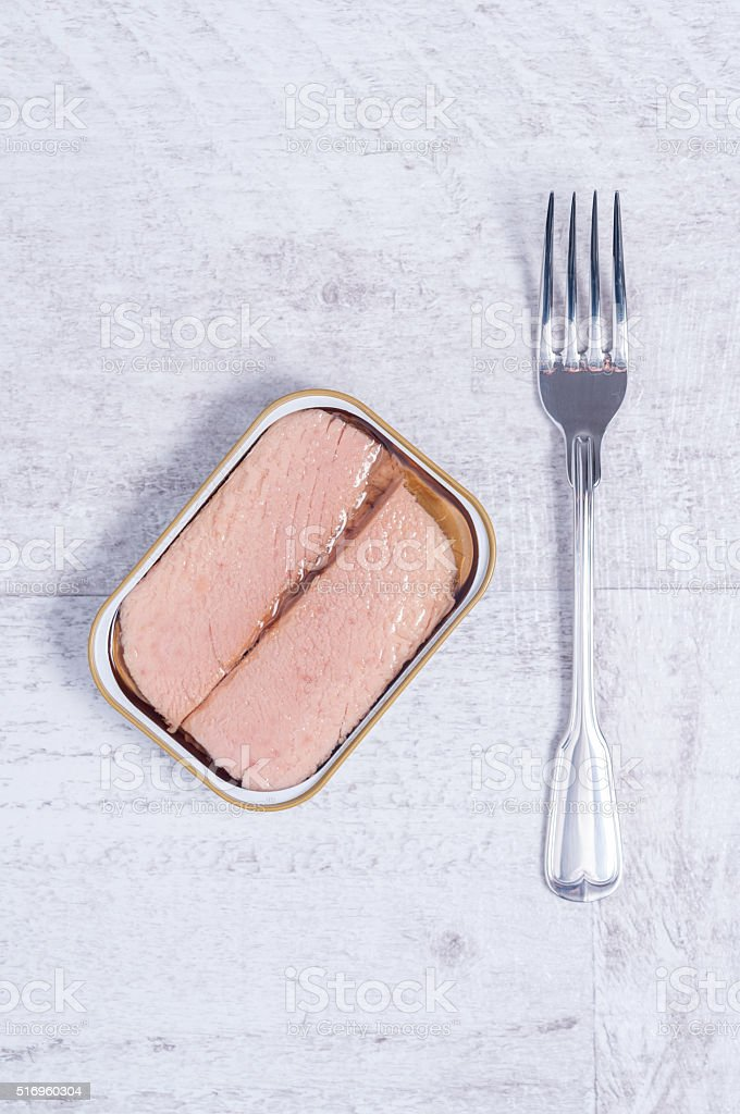 canned tuna on a wooden table stock photo