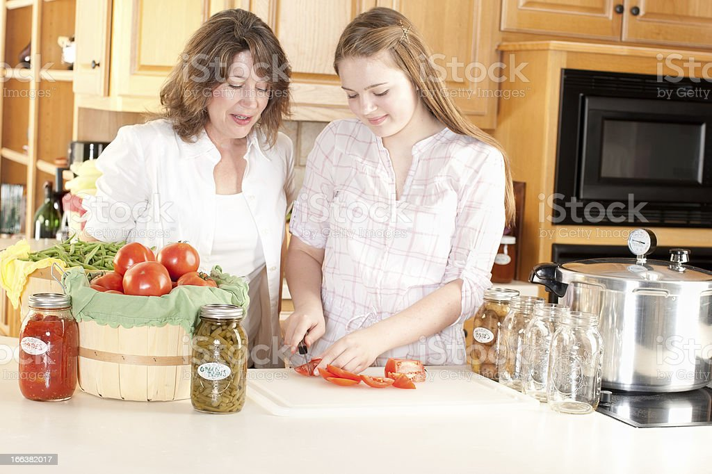 Canning: Caucasian Mother Helping Teenage Daughter Preserve Homegrown Fruits Vegetables royalty-free stock photo