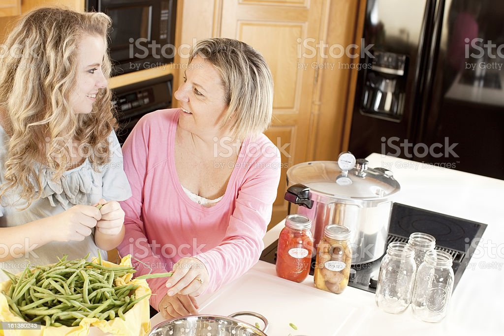 Canning: Caucasian Mother Teenage Daughter Preserving Homegrown Fruits Vegetables stock photo