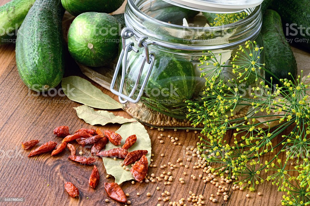 canning cumbers with spices like bay leaf and chilie stock photo