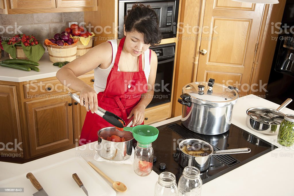 Canning: Mixed Race Young Adult Woman Preserving Homegrown Fruits Vegetables stock photo