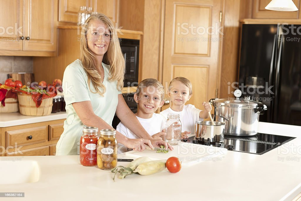 Canning: Mother Sons Preserving Homegrown Fruits and Vegetables royalty-free stock photo