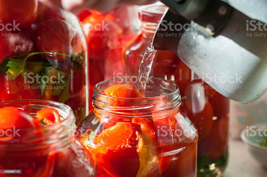 Canning process of tomato in mason jar. On background is stock photo