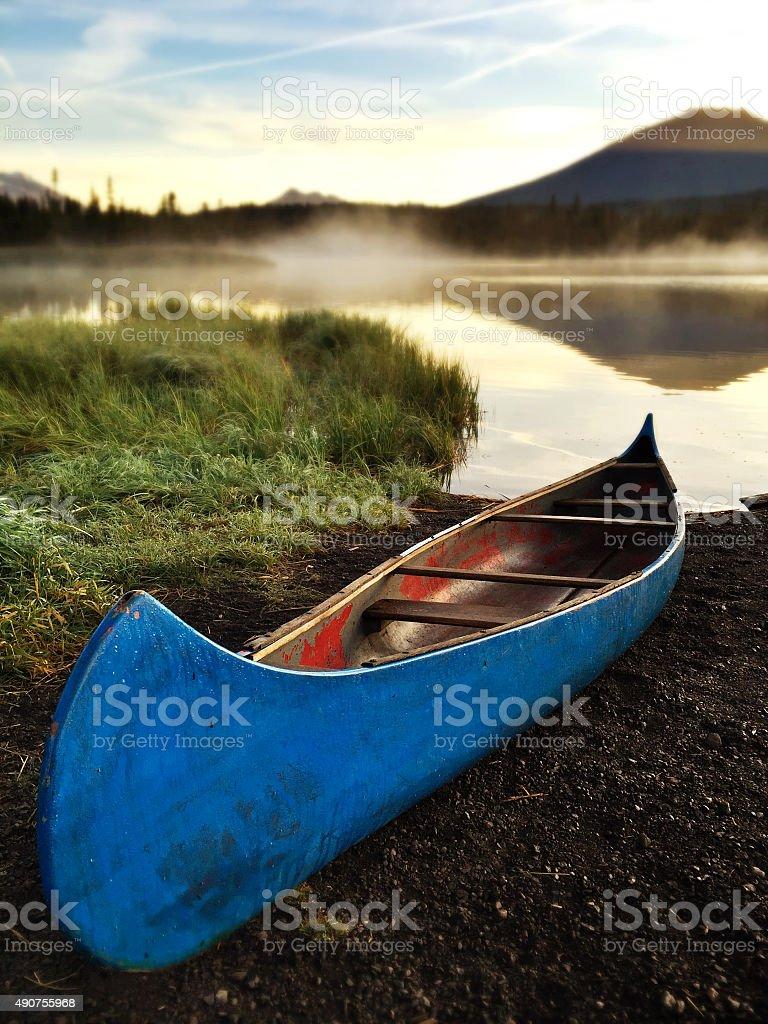 Canoe at edge of lake at dawn stock photo