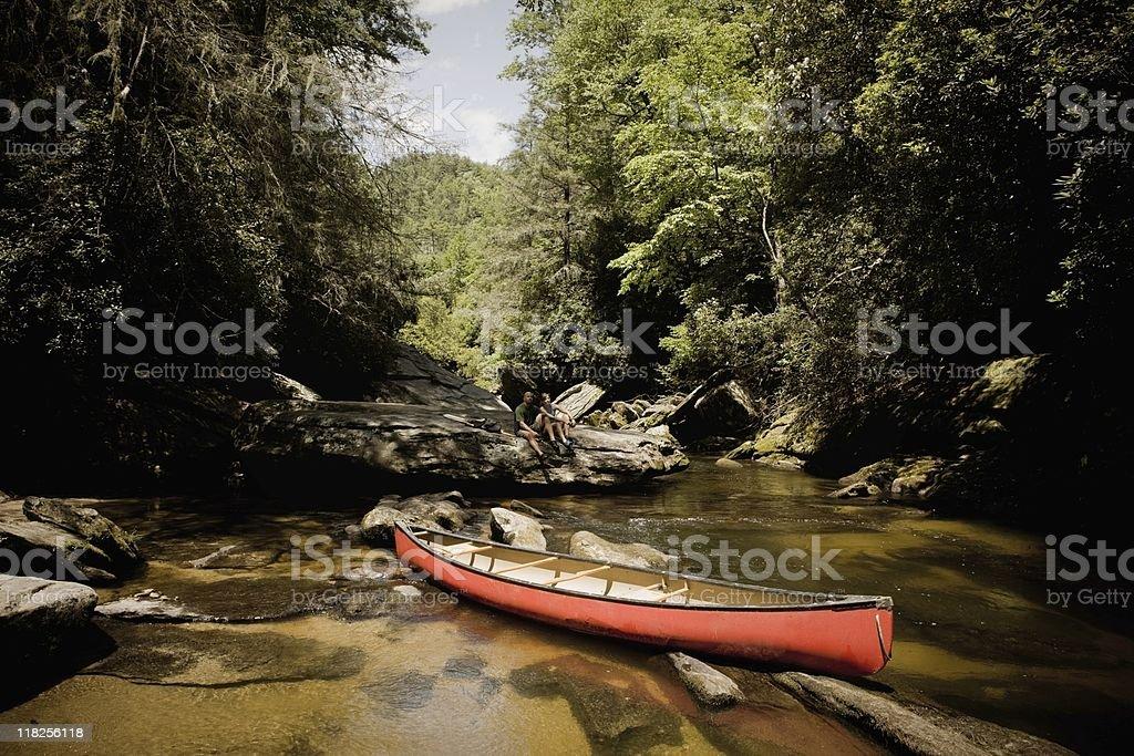Canoe Couple Taking Break on Boulder royalty-free stock photo