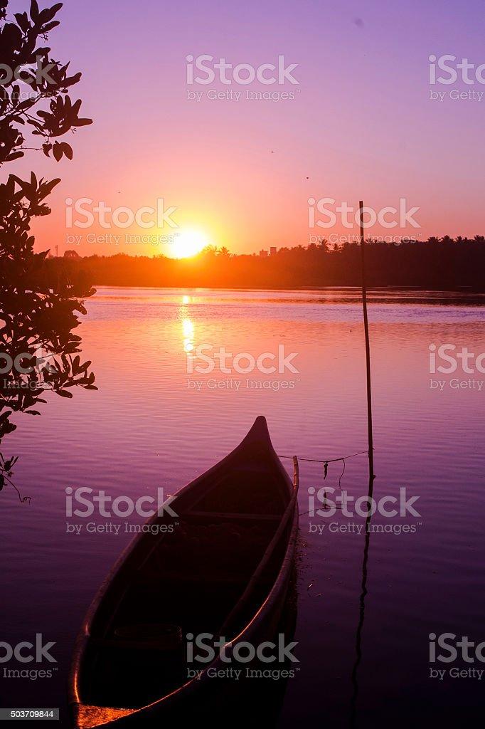 Canoe in lake at sunset stock photo