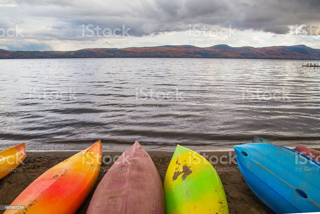 Canoe in lake with cloud and Autumn forest in background stock photo
