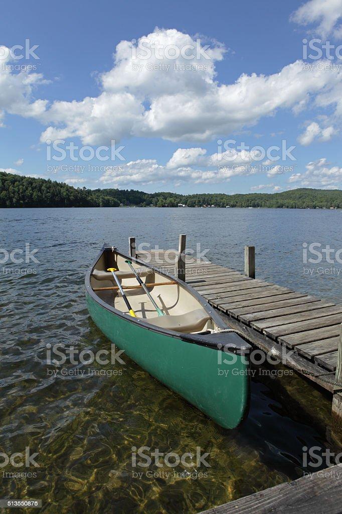 Canoe on a lake beside a jetty stock photo