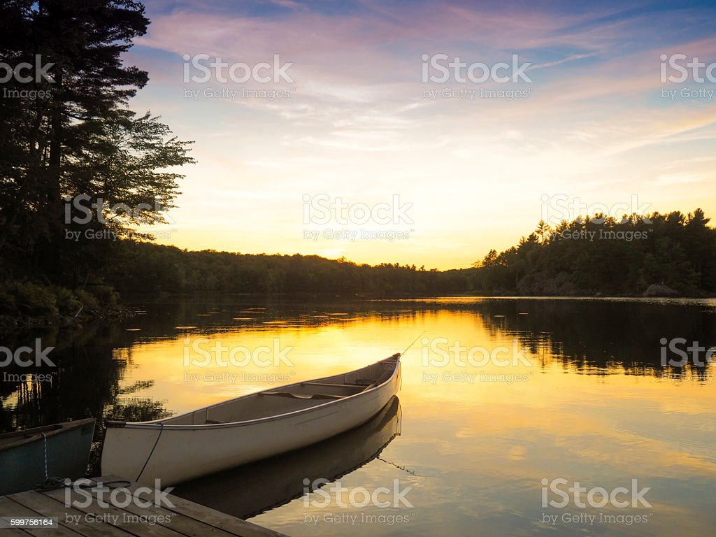 Canoe on a northern lake at sunset stock photo