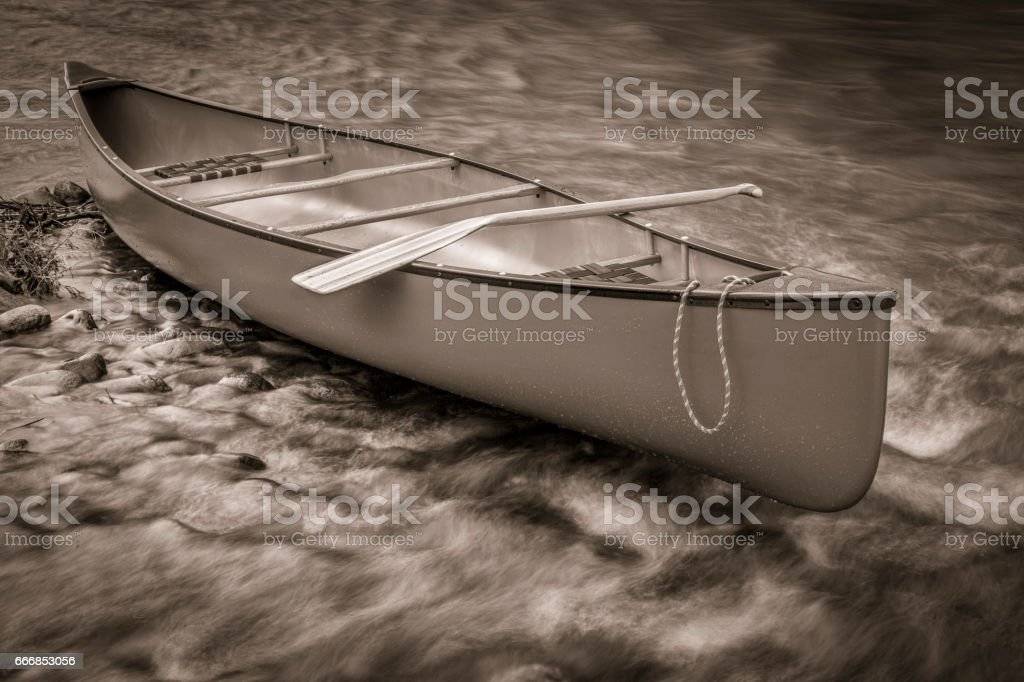 canoe on a shallow rocky river stock photo