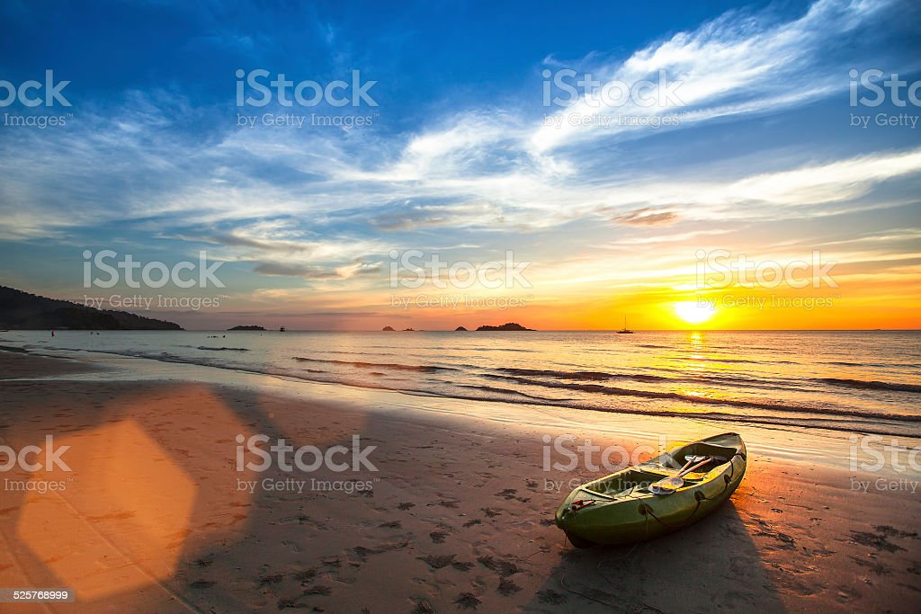Canoe on the ocean beach during the amazing sunset. stock photo