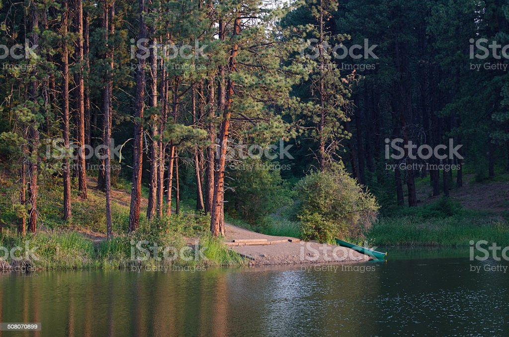 Canoe Resting on Remote Lake's Shore as Early Morning Dawns stock photo