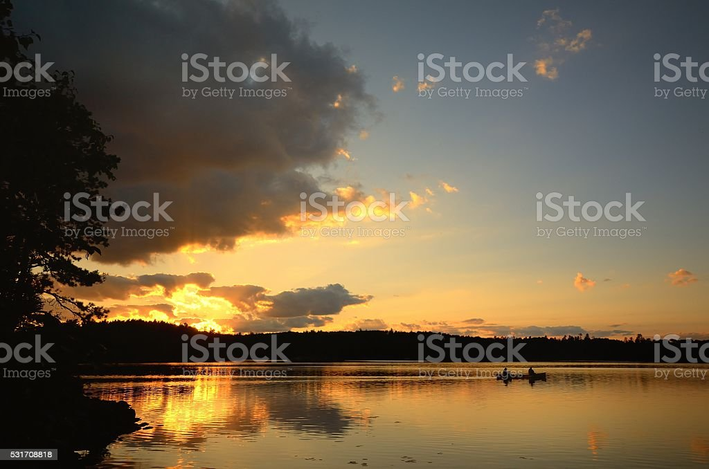 Canoeing at Sunset on a Wilderness Lake stock photo
