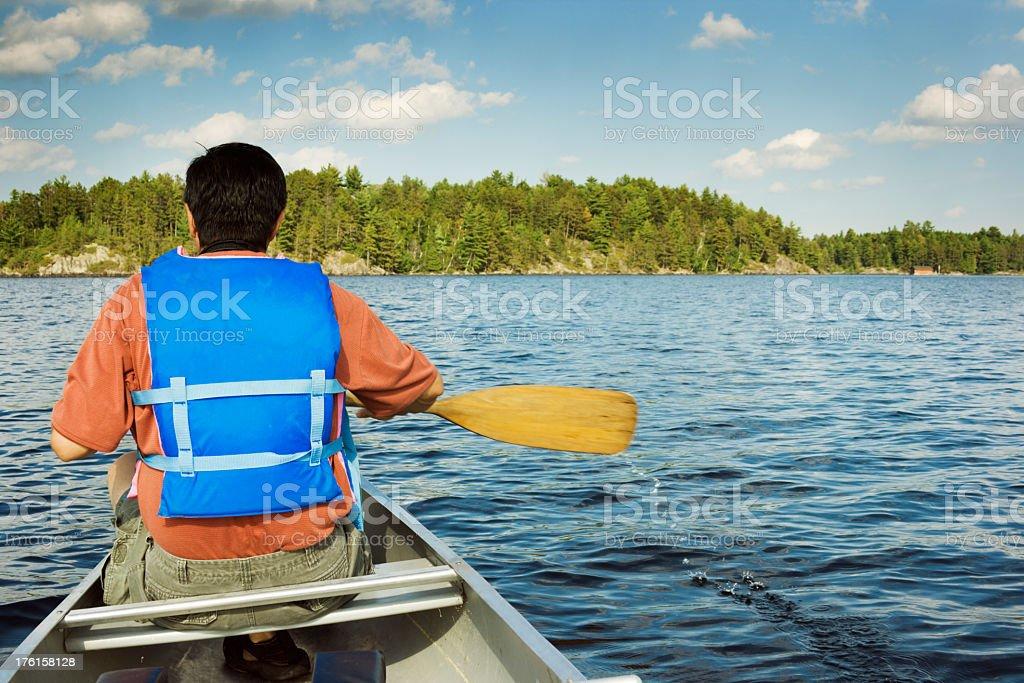 Canoeing Man Near Boundary Waters Canoe Area Lake, Back View royalty-free stock photo