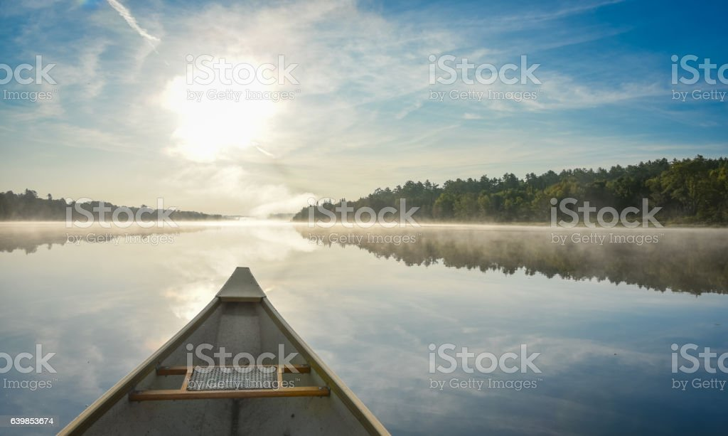 Canoeing on a misty summer morning on Corry Lake. stock photo
