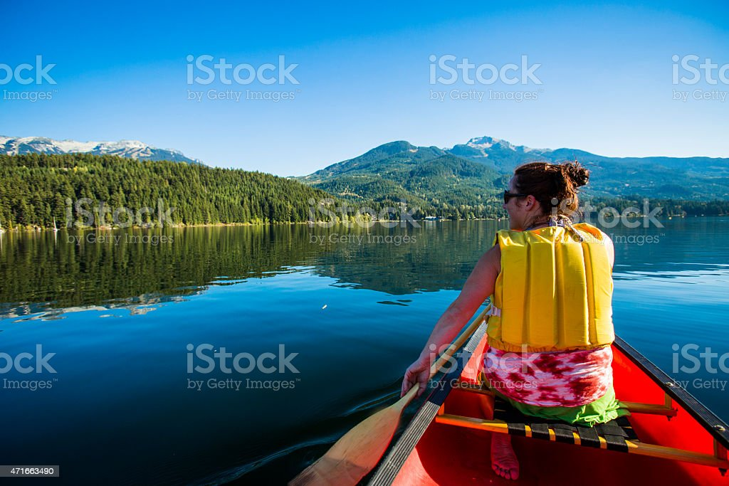 Canoeing on calm lake in Whistler. stock photo