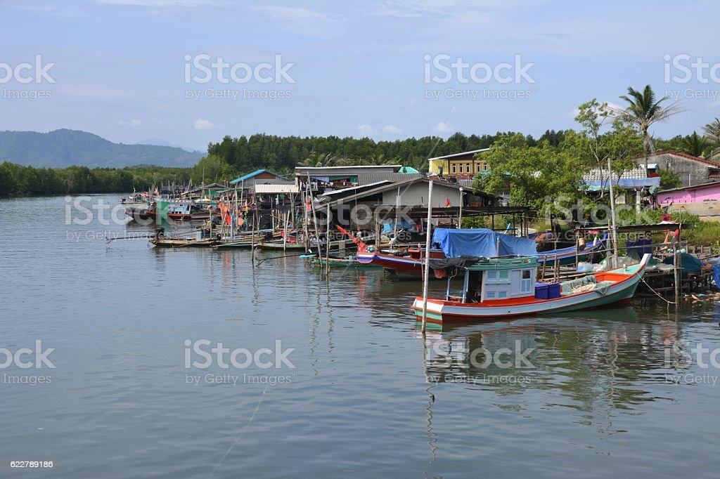 Canoes and fishing boats moored at Khanom village, Southern Thailand stock photo