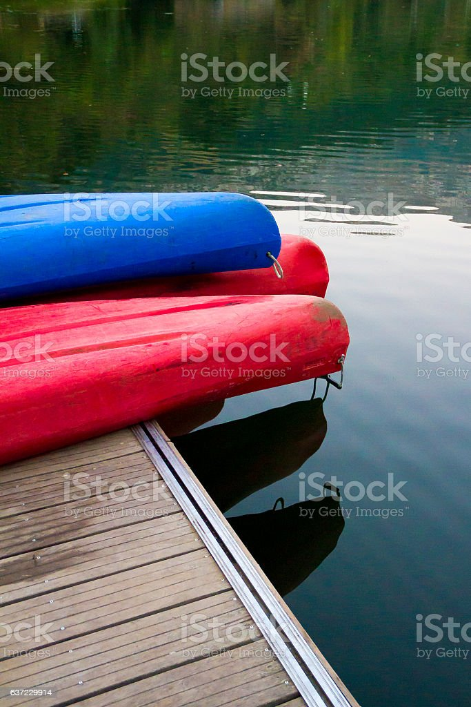 Canoes on a dock next to a lake stock photo