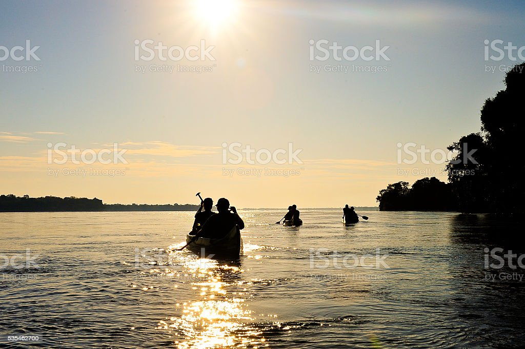 Canoing into the setting sun stock photo